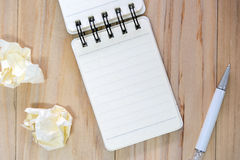 Small note book paper notepad for writing information with pen and crumpled paper balls on wooden table Royalty Free Stock Photo