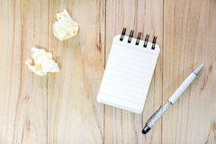 Small note book paper notepad for writing information with pen and crumpled paper balls on wooden table. View from above Stock Photos