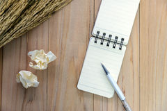 Small note book paper notepad for writing information with pen and crumpled paper balls on wooden table. View from above Stock Photography