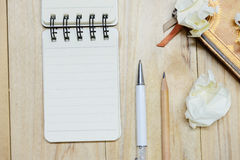 Small note book paper notepad for writing information with pen, pencil, book and crumpled paper balls on wooden table Royalty Free Stock Images