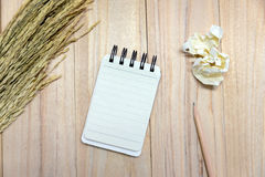 Small note book paper notepad for writing information with pencil and crumpled paper balls on wooden table. View from above Stock Images