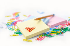 Small note pad and a pencil on a background of multi-colored paper clips. Royalty Free Stock Images