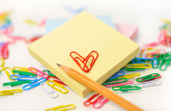 Small note pad and a pencil with colored paper clips on white. Stock Image