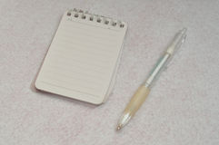 A small note pad with a white pen Stock Photos