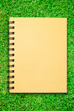Small notebook on green grass field Stock Photo