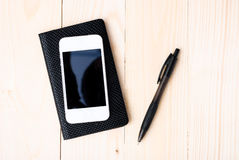 Small notepad with pen and smartphone Royalty Free Stock Image