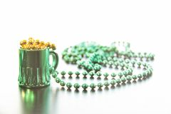 St Patricks Day Mini Green Mug Gold Beads. A small novelty green mug necklace with gold beads. In the style of St Patrick`s Day Royalty Free Stock Photography