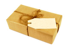 Small oblong brown paper package tied with string, blank manila address label Royalty Free Stock Images