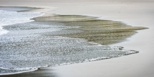 Small ocean sea waves on sandy beach in calm weather. Stock Images