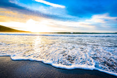 Small ocean sea waves on sandy beach with sunrise sunset. Stock Image