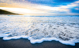Small ocean sea waves on sandy beach with sunrise sunset. Royalty Free Stock Image