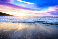 Small ocean sea waves on sandy beach with sunrise sunset. Background landscape picture of dusk or dawn at the Atlantic ocean beach with small waves at low tide Royalty Free Stock Photos