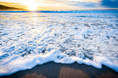 Small ocean sea waves on sandy beach with sunrise sunset. Royalty Free Stock Photo