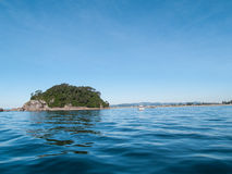 Small off-shore island across blue of ocean from low point of view with Mount Maunganui Royalty Free Stock Photos