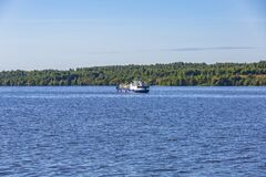 Small oil tanker on the water near the forest coast