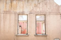 Small old and abandoned damaged house cracked windows without roof demolished by the earthquake destruction closeup.  Stock Image
