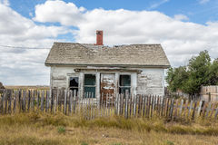 Small old abandoned house with a broken picket fence in summer time. Royalty Free Stock Images