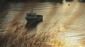 Small old boat anchored on sea near coastline at sunset. wind sways grass on the shore. reflection on the water glare. Concept of loneliness and sadness stock video