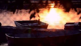 Small Old boat moored near old wooden pier jetty. Black leaf silhouettes. Bright white-yellow spot of reflecting sun on surface of water. Calm weather with stock video