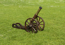 Small old cannon on the lawn overgrown with daisies (Béllis per Stock Images