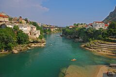 Small old city between Neretva River with clean clear water surrounded by green trees in Bosnia and Herzegovina