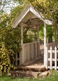 A small old covered wooden bridge with yellow climbing roses growing all around it stock photo