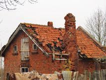 Small old falling home in village, Lithuania. Small old falling red bricks home in village in spring royalty free stock photos