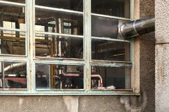 Small old heating plant windows from outside. Heat pipes covered in silver foil visible behind glass stock photo