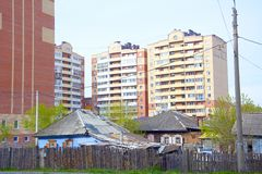 Small old houses, on the background of modern high-rise buildings.  royalty free stock images