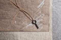 A small old key lies on a wooden board. Minimalistic still life Stock Images