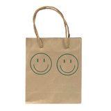Small and old paper bag with green smile face isolated on white Stock Image