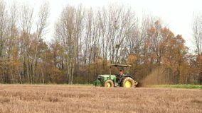 Small old tractor is repairing and deepening the drained channel in wet field. Tractor with cutter is working. stock video footage
