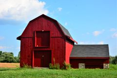 Small old two story red barn with annex under sunny blue skies on a hot and humid summer day. Azure fluffy white cirrus clouds , green grass field Hillsborough Stock Image