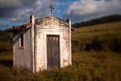 Small old white church in the countryside - titl-shift lens. Small old white church in the countryside in a blue sky day - titl-shift lens royalty free stock photo