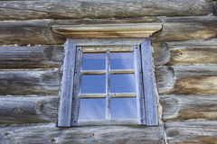 Small Old window with glass with a blue sky on the background of the wooden wall of the countryside log house Stock Photography