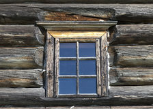 Small Old window with glass with a blue sky on the background of the wooden wall of the countryside log house Stock Photos