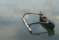 A small old wooden Balinese boat, blue paint on the side, broken seats, on the left a large counterweight, stands on the water, wh Stock Images