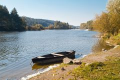 Small old wooden fishing boat punt on the bank of a river, bright sunny day, forest in background. Small old wooden fishing boat punt on the bank of a river royalty free stock photos