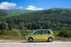 Small olive green car. Against the background of mountain landscape Stock Photography