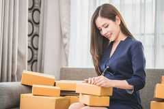 Small online business owner writing package for delivery Royalty Free Stock Images
