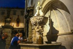 Small Onofrio Fountain in Dubrovnik. DUBROVNIK, CROATIA - JULY 22, 2017 : A woman giving water to a cat from the Small Onofrio Fountain in the city center of Stock Photography