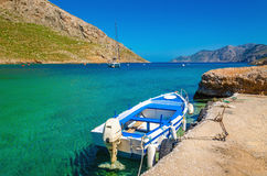 Small open-deck motor boat in Greek colors in port at the bay of. Greek Island, Greece Royalty Free Stock Photos