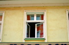 Small open window with yellow facade Stock Photos