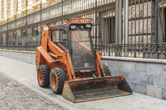 Small orange bulldozer machinery used for cleaning by municipali Stock Images