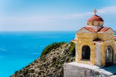 Small orange colored Hellenic shrine Proskinitari on the cliff edge with defocused sea view in the background.  stock photo