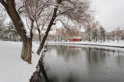 Small orange cottage and trees under the snow,. Riverside, park, outdoor Royalty Free Stock Photo