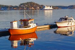 Small orange fishing boat with reflection in the water Royalty Free Stock Photography