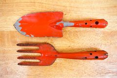 Small orange gardening fork and shovel on wooden board background. Texture royalty free stock image