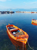 Small Orange Greek Fishing Boat. A small hand made wooden Greek fishing boat, or caique, painted with bright orange marine protective paint, with nets and floats Royalty Free Stock Photo