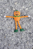 A small orange halloween pumpkin doll on the road Royalty Free Stock Photography